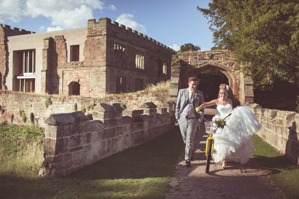Bride and groom with yellow bike at Astley Castle
