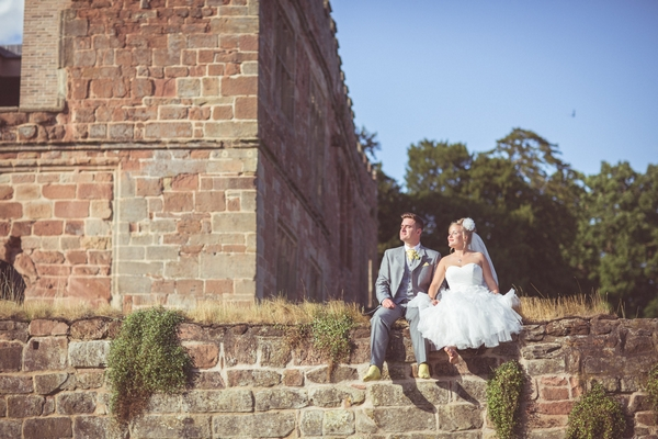 Bride and groom sitting on wall at Astley Castle