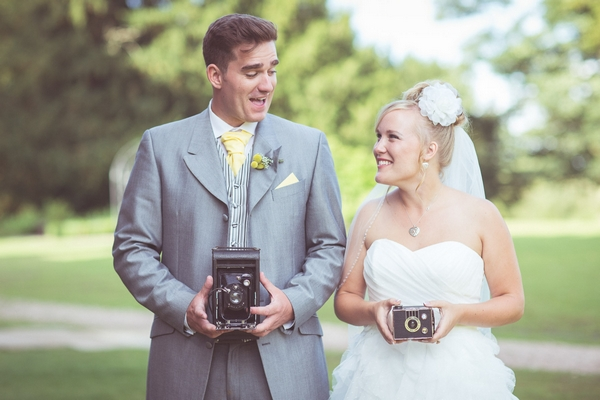 Bride and groom holding vintage cameras