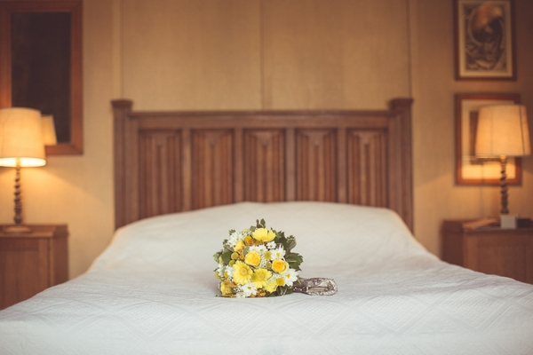 Yellow bridal bouquet on bed