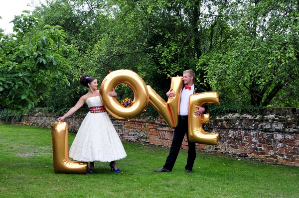 Bride and groom carrying gold love letters