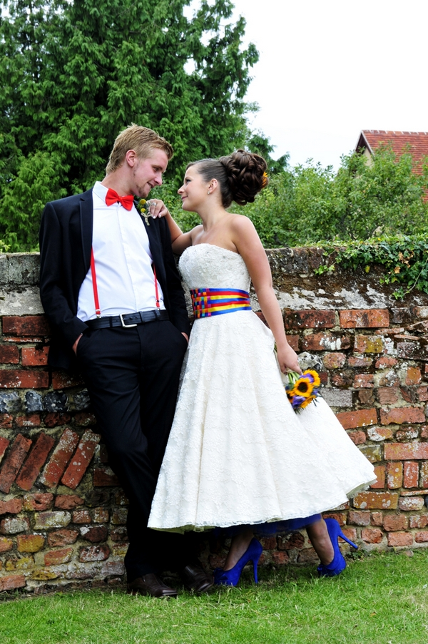 Bride and groom standing by wall