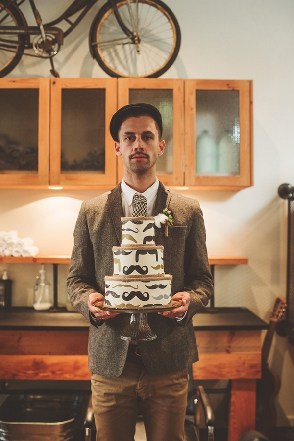 Vintage groom holding Movember wedding cake