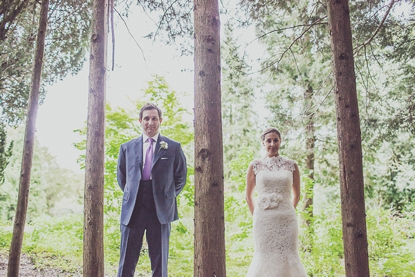 Bride and groom standing amongst trees
