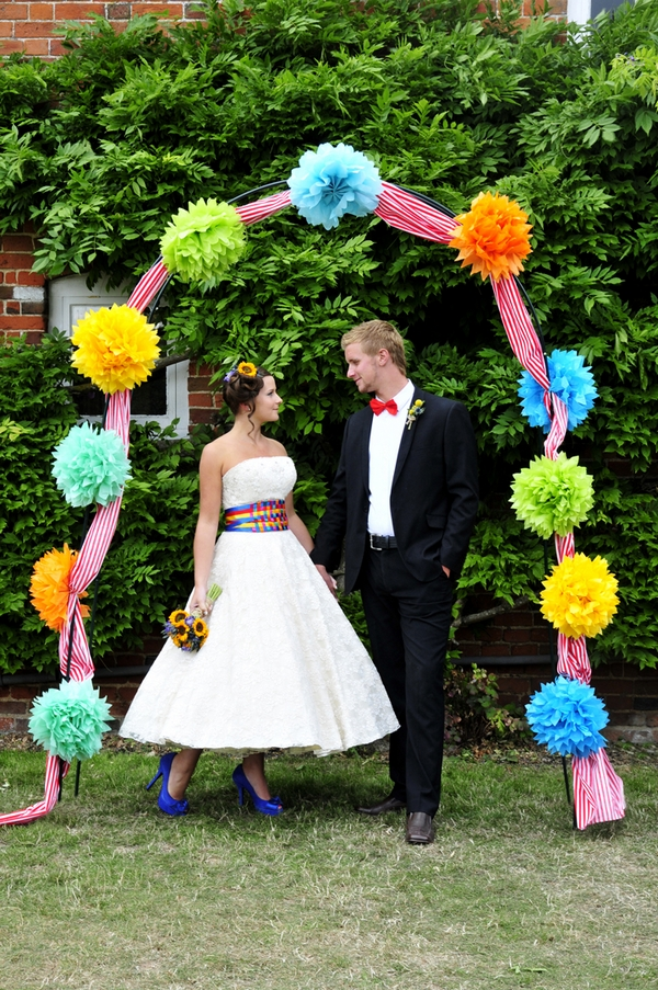 Bride and groom under arch of pom poms