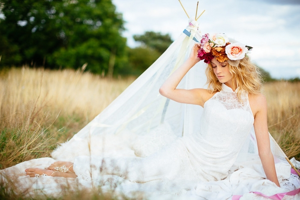 Boho bride laying in front of small tipi
