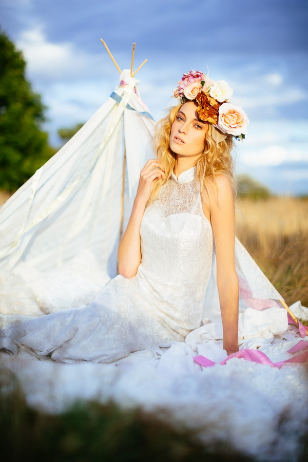 Boho bride with flower crown in front of tipi