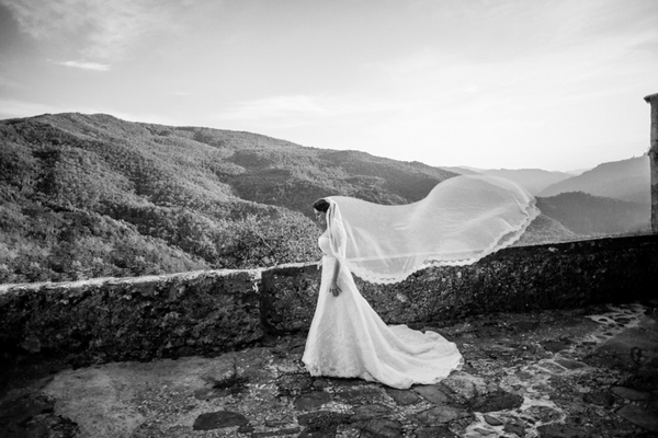Bride standing by hills with veil blowing in the wind - Picture by Jo Hone Photography