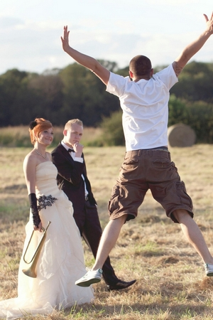 Voyteck of Voyteck Photography jumping in front of bride and groom