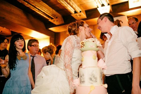 Groom feeding bride wedding cake