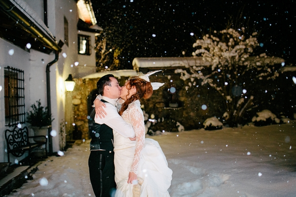 Bride and groom kiss in snow at night