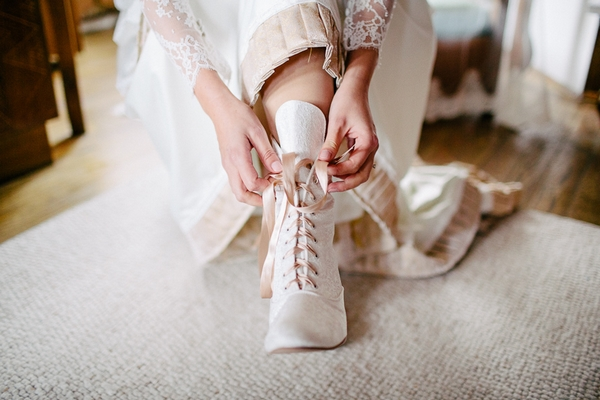 Bride putting on bridal boots