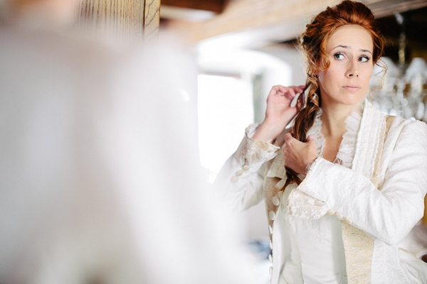 Bride adjusting hair in mirror