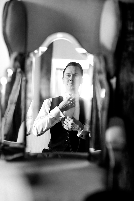 Groom adjusting cravat in mirror