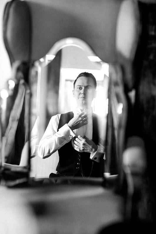 Groom adjusting cravat in mirror