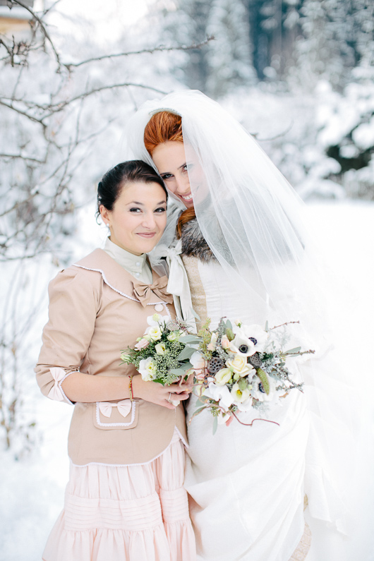 Bride and bridesmaid in snow