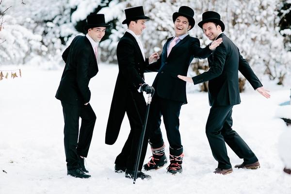 Groomsmen with top hats in snow