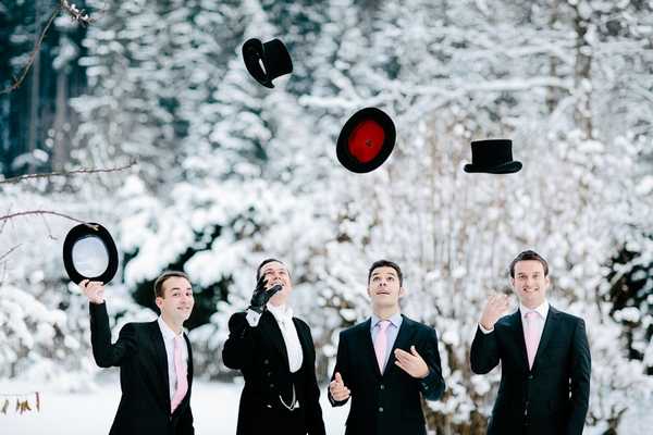 Groomsmen throwing top hats in air