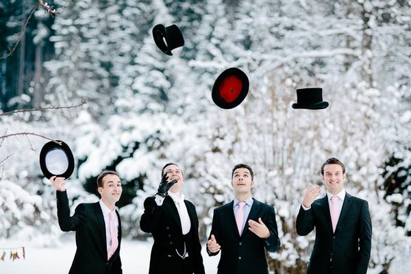 Groomsmen throwing top hats in air