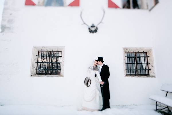 Bride and groom in front of Schloss Münichau in snow