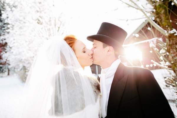 Bride and groom kiss in snow