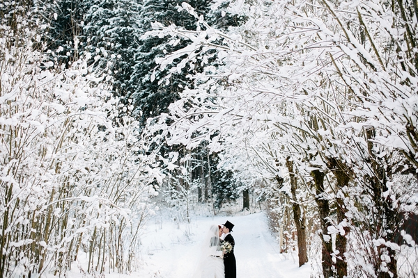 Bride and groom standing in snow