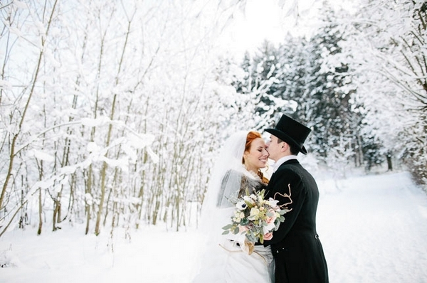 Groom kissing bride in snow