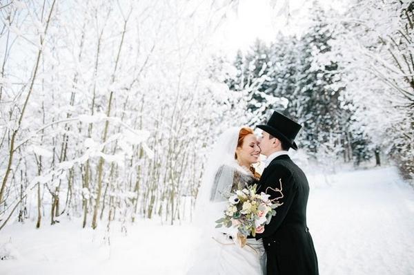 Groom kissing bride in snow