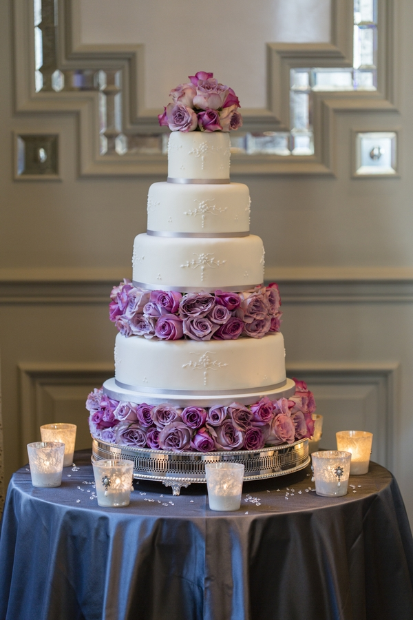 Tiered wedding cake with purple flowers