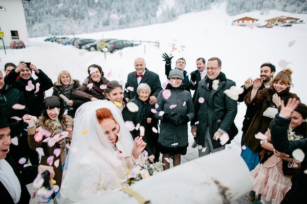 Bride being showered in confetti in snow
