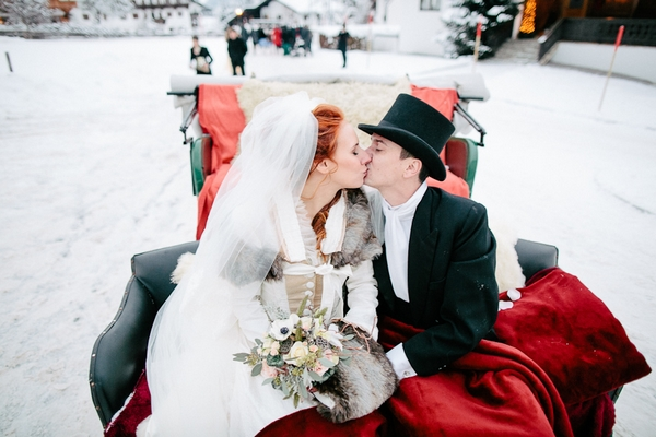Bride and groom kiss in back of horse and carriage