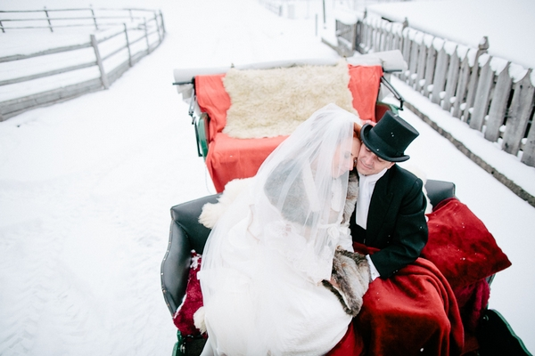 Bride and groom in back of horse and carriage