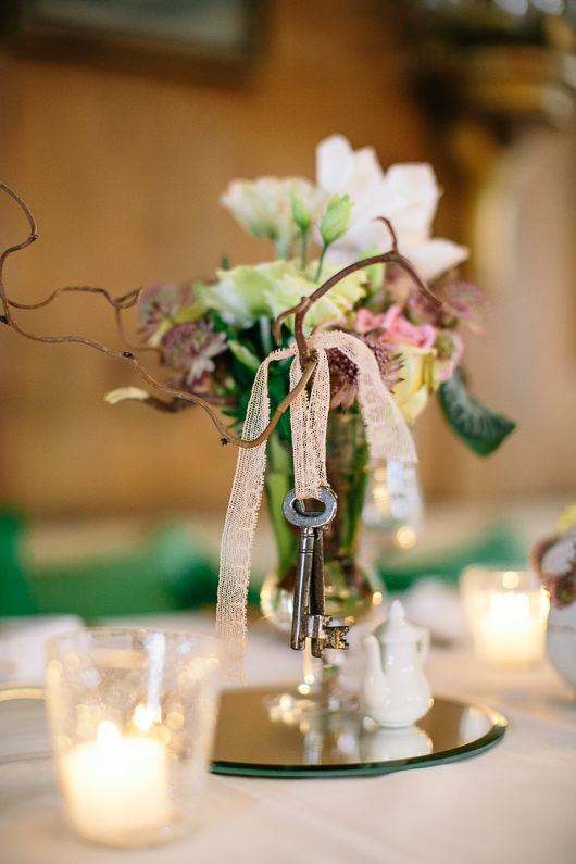 Key hanging from vase of flowers