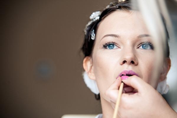 Bride applying lip gloss