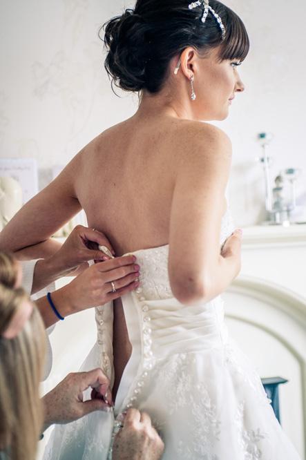 Bride having wedding dress done up