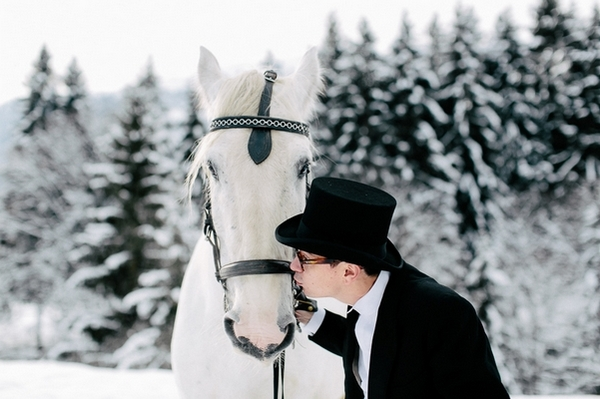 Groom kissing horse