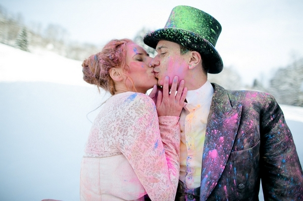 Bride and groom kiss covered in holi powder in the snow