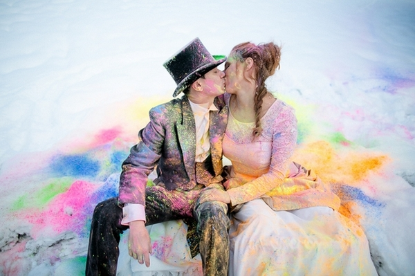 Bride and groom covered in holi powder sitting in the snow