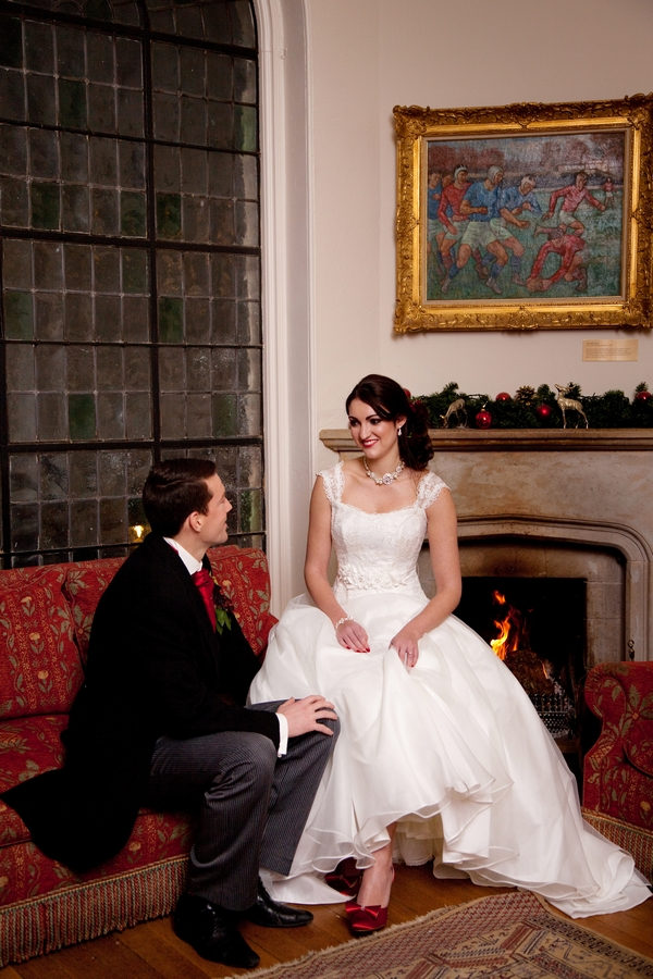 Bride and groom sitting by fire