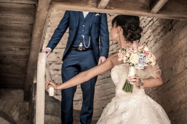 Bride walking down steps looking back at groom