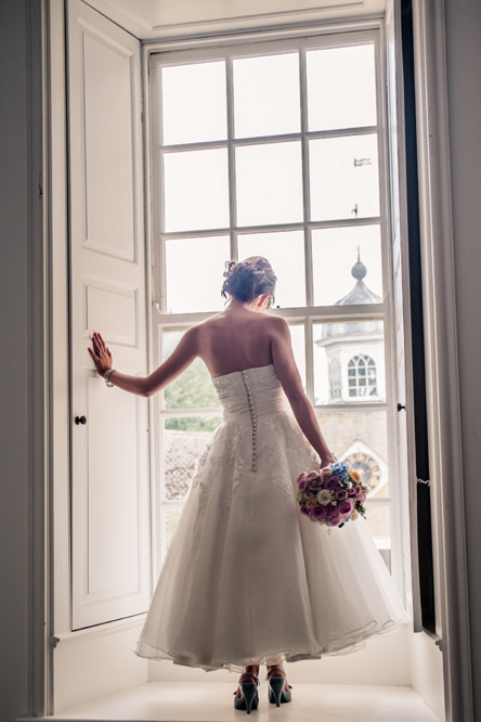 Bride standing at window