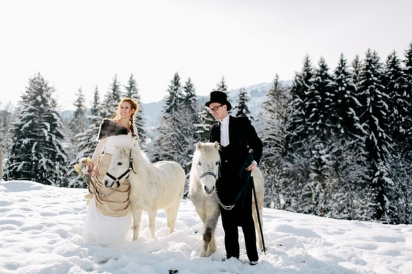 Bride and groom in snow with horses