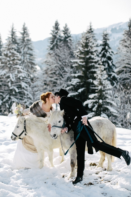 Bride and groom leaning over horses to kiss