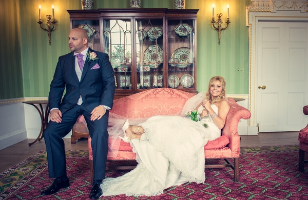 Groom sitting on edge of sofa bride is laying on