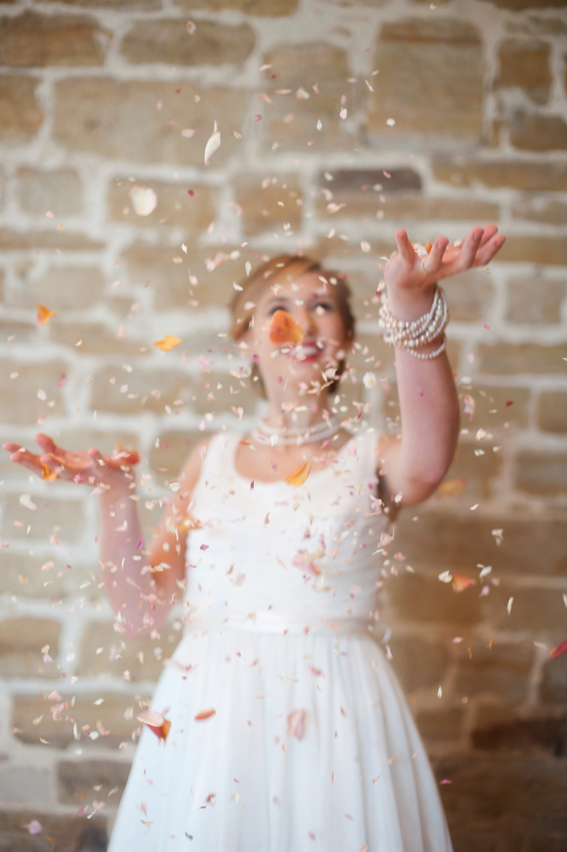 Bride throwing confetti in air