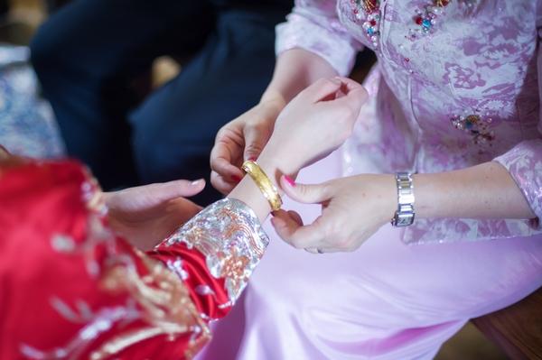 Bride putting bracelet on