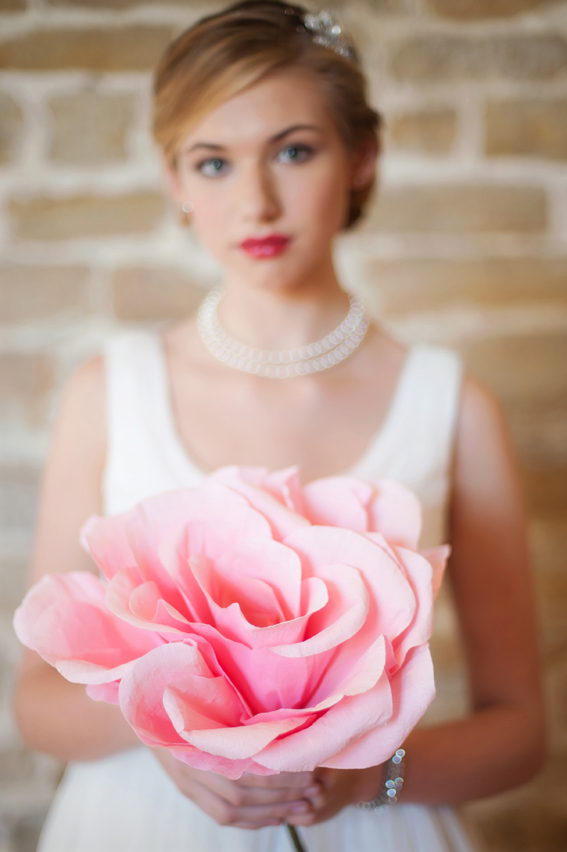 Bride holding large pink flower