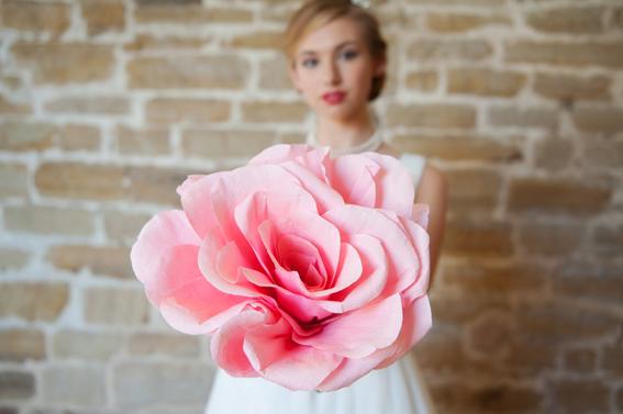Bride holding large pink flower