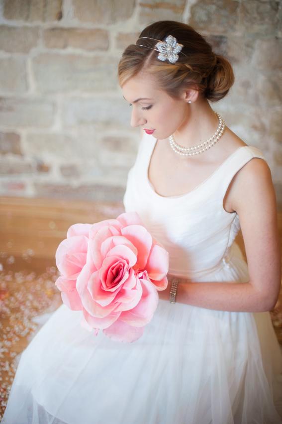 Bride sitting holding large pink flower