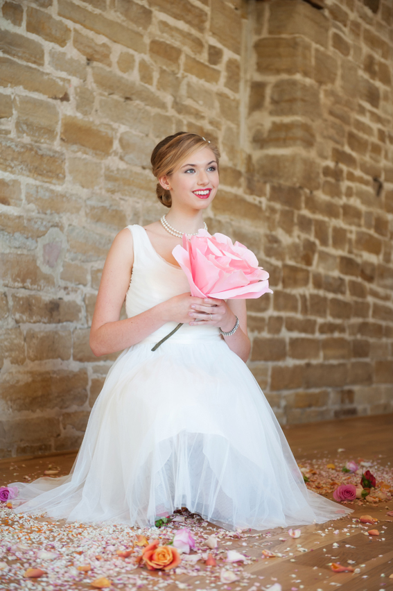Bride sitting holding large pink flower